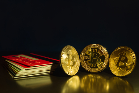 Bitcoin three coins closeup on reflective surface with dark blue background and stack of credit cards Stock Photo
