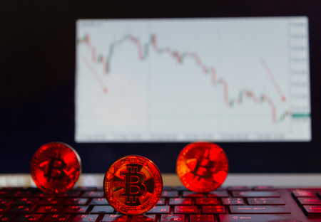 bitcoin on the keyboard in red, on the background of the descending chart Stock Photo