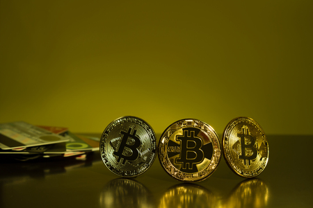 Bitcoin three coins closeup on reflective surface with dark yellow background Stock Photo