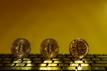 Bitcoin on black keyboard three coins of gold color on a yellow background