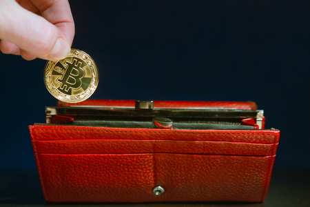 In a red wallet on a blue background, a person puts a bitcoin coin with his fingers Stock Photo