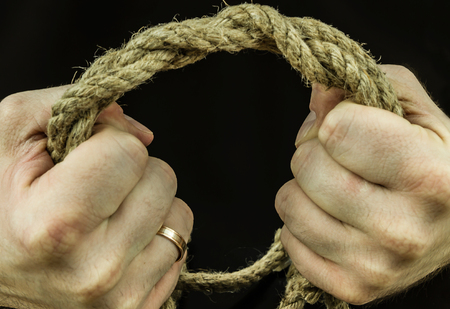 Braided coconut rope in the hands of men in tension squeezing Stock Photo
