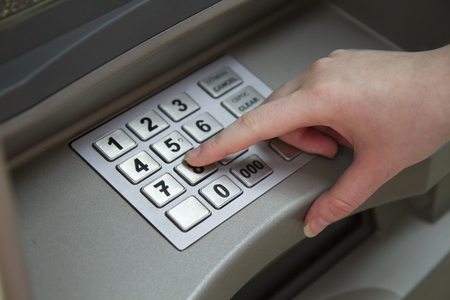 Close-up of hand entering PIN pass code on ATM bank machine keypad Stock Photo
