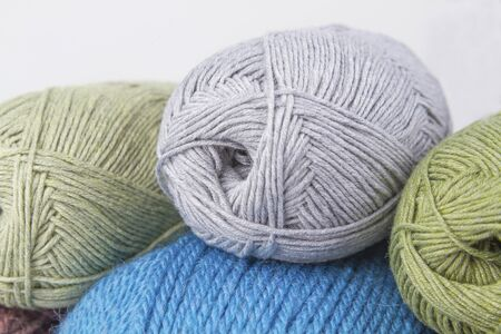uterus for knitting with hands of wool. Several pieces gray green blue. Stock Photo
