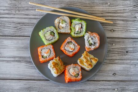 plate with a variety of sushi rolls and chopsticks seen Stock Photo
