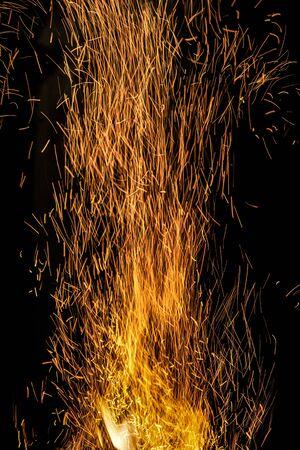 many bright orange burning sparks rise up