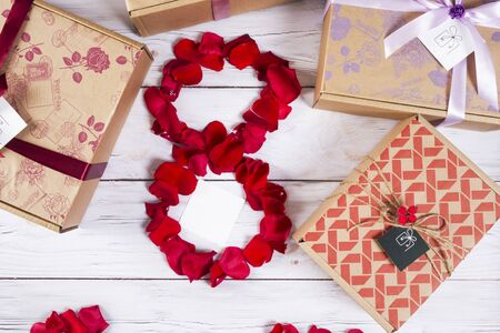 Holiday eighth of March, red rose petals laid out in the form of the number eight. International women day. Wooden background light grey Stock Photo - 137674956
