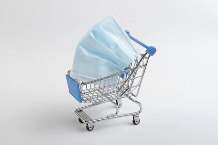 protective mask in a shopping cart on a white background Stock Photo