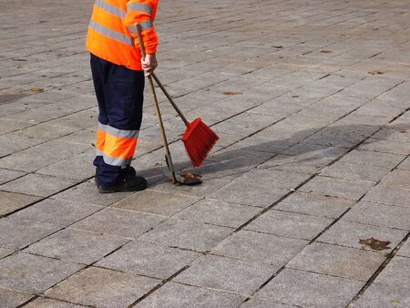 Harvesting leaves on a city square lined with stone slabs. Worker in uniform sweeping leaves on the street. Clean with a broom and dustpan. Selective focus.