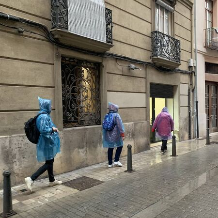 Three tourists with backpacks in raincoats walk on a city street. Social distance during a pandemic. Street photo. Rainy day.
