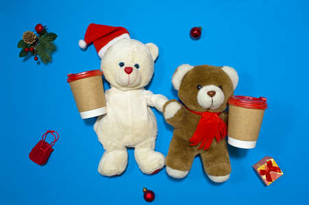 Christmas childrens composition. Two fluffy teddy bears are holding paper cups of hot drink in their paws. Traditional soft toys made from faux fur. Flat lay. View from above.
