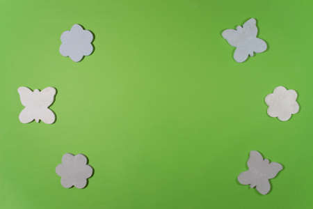 Sketchy rustic wooden figurines of flowers and butterflies on a green background. Childrens toys for decorating. Flat lei. Copy space for text, frame. 版權商用圖片