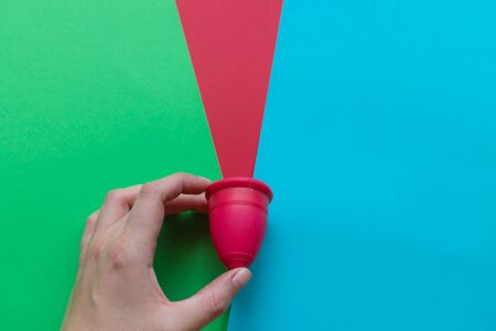 Close up of woman hand holding menstrual cup over colorful background. Women health concept, zero waste alternatives. Imagens