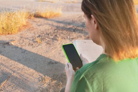 woman holding her smartphone with a green case. Copy space. Focus selected.