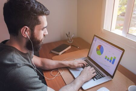 Young man with beard and earphones, working with his laptop with report and graphics on the screen. Wood desk, window lights. Home office.Work from home concept.
