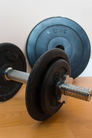Dumbbell with black discs on wooden platform. Training at home concept.