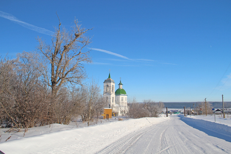 latticed: beautiful white-stone village church in the village of Shigali, Chuvash Republic, Russia in winter against the background of blue sky and snow-white drifts Stock Photo