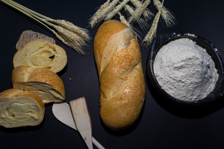 still life of bread and wheat flour on black background decorated with spikes