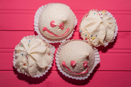 meringues with colorful sparks and happy wands on pink wooden background and space to place text