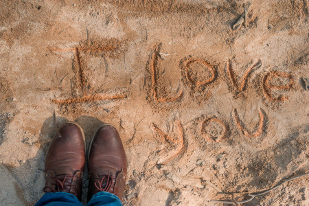 phrase i love you written in the sand next to man feet with old shoes