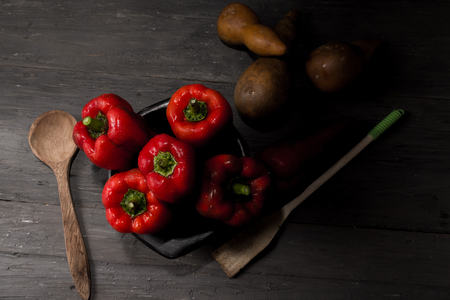 FRESH RED PEPPERS IN THE FOREGROUND IN BLACK CLAY BOWL ON RUSTIC WOOD TABLE
