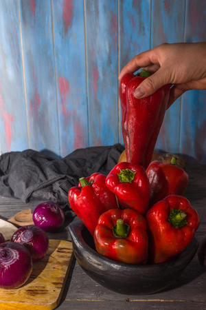 STILL LIFE OF RED PEPPERS BEING PLACED BY WOMAN'S HAND OVER RUSTIC BOWL ACCOMPANIED BY ONIONS AND DECORATED WITH OLD CLOTH