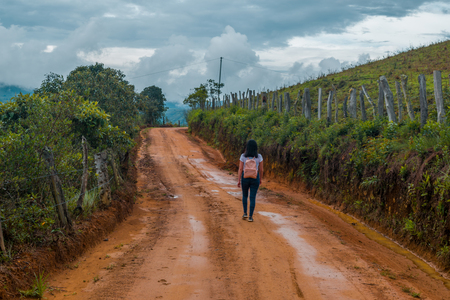 young woman walking alone in rural road over the mountains of colombia wearing sport clothes and pink backpack 写真素材