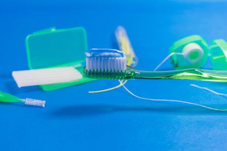 OBJECTS FOR TEETH CLEANING AND ORTHODONTIC CARE WITH TOOTHPASTE ON THE TOOTHBRUSH ON BLUE BACKGROUND