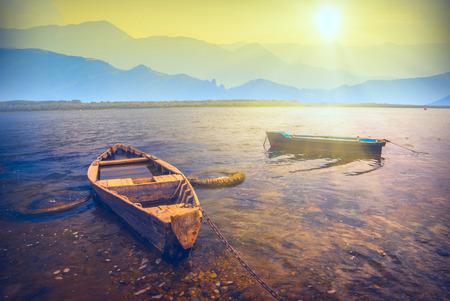 Lever de soleil sur un grand lac avec des bateaux en bois rustiques dans une vallée de montagne brumeuse Banque d'images - 35912824