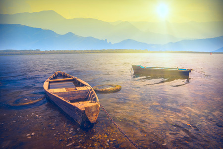 Sunrise on a big lake with rustic wooden boats in a foggy mountain valley Imagens