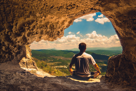 meditates: The man who meditates in a cave overlooking the mountain valley