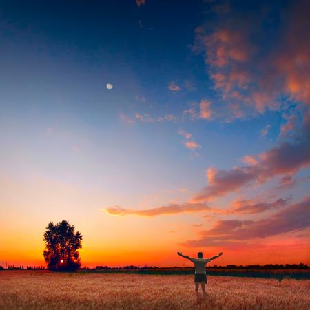 Humaine dans un champ de blé profiter le coucher du soleil lumineux et coloré Banque d'images - 36631591