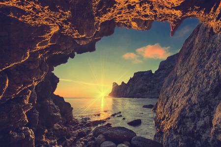 paisagem: Por do sol do mar do vintage da caverna na montanha