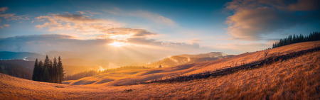 panorama: Panorama of sunset in a Carpathian mountain valley with wonderful gold light on a hills