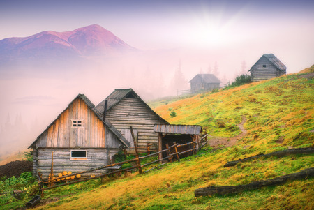 Sunrise above the nature wooden houses in a Carpathian mountains with highest mountain of Goverla, Ukraine