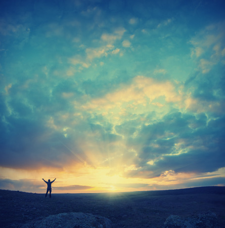 sunrise: Vintage picture. Men, who welcome sunrise with raised hands and enjoying landscape.