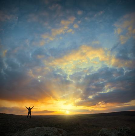Les hommes, qui accueillent le lever du soleil avec les mains levées et le paysage profiter. Banque d'images - 36865542
