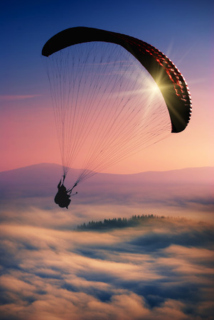 paraglide: Paraglide silhouette over misty mountain valley.