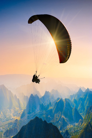 paraglide: Paraglide silhouette over mountain peaks.