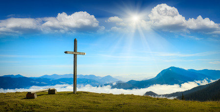 Place for rest with christian cross on a top of mountain above the sunny foggy valley. Carpathian mountains, Ukraine.