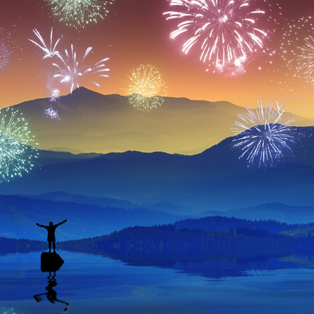 Men, who stending on a rock in a mountain lake and welcome firework with raised hands Imagens