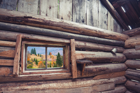 View from window of rustic wooden house to Carpathian mountain village. Ethnic cottage Stock Photo