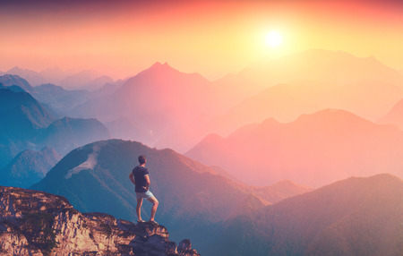 peak: Man standing on a mountain top and enjoy sunrise in a Carpathian mountains Stock Photo