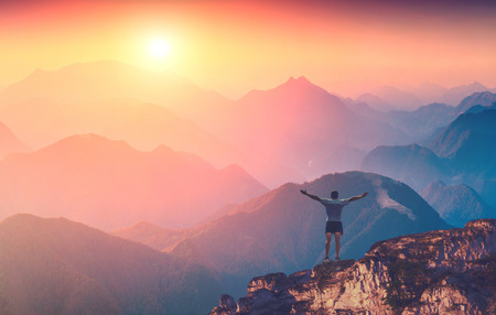 mountain valley: Man with raised hands standing on a mountain top and welcome sunrise in a Carpathian mountains Stock Photo