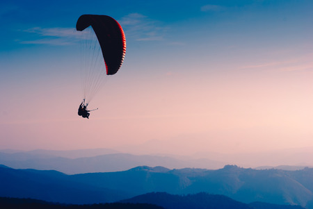 paraglide: Paraglide silhouette over mountain Carpathian valley.