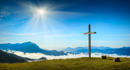 wooden cross: Place for rest with christian cross on a top of mountain above the sunny foggy valley. Carpathian mountains, Ukraine.