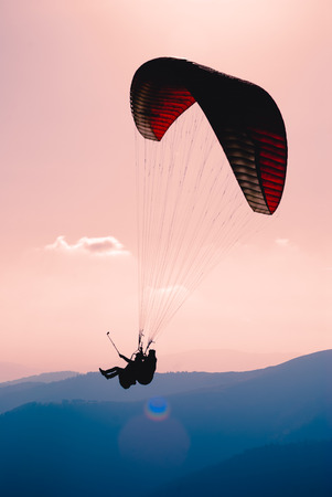Paraglide silhouette flying over Carpathian peaks and clouds