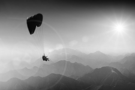 paraglide: Paraglide silhouette over mountain peaks. Monochrome colors Stock Photo