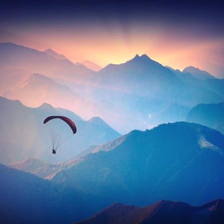 高山日の出の光の上を飛ぶパラグライダーで飛ぶのシルエット。ウクライナのカルパチア バレー。