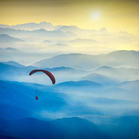 paraglide: Paraglide silhouette in a light of sunrise above the misty Crimea valley.